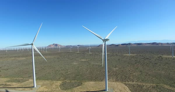 A high angle aerial over a Mojave desert wind farm as it generates clean energy for California. Royalty-free stock video