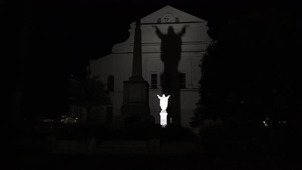 A statue of Jesus is made large in shadow at night on St. Louis church in Jackson Square, New Orleans. Royalty-free stock video
