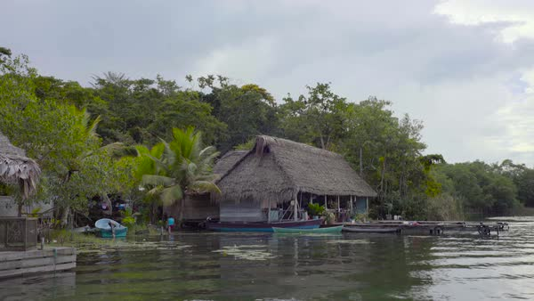 View from a boat of a village huts on stilts along a river in Guatemala. Royalty-free stock video