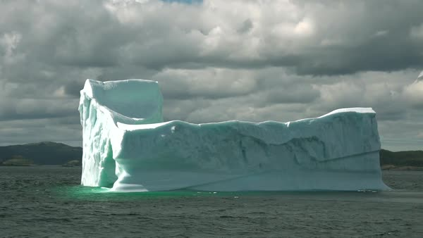 Real time flow of sea ice floating past grounded icebergs in Newfoundland waters. Royalty-free stock video