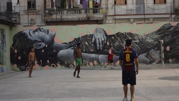 Poor kids play soccer in front of a beautiful mural in Havana, Cuba. Royalty-free stock video
