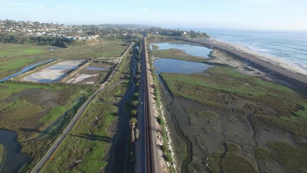 Aerial over an Amtrak train traveling beside the Pacific ocean near San Diego. Royalty-free stock video