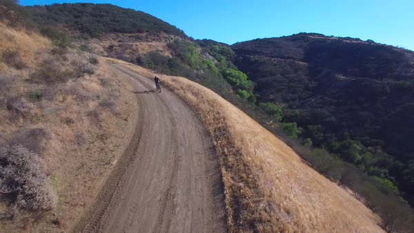 Good aerial following shot of a mountain biker riding fast down a mountain. Royalty-free stock video