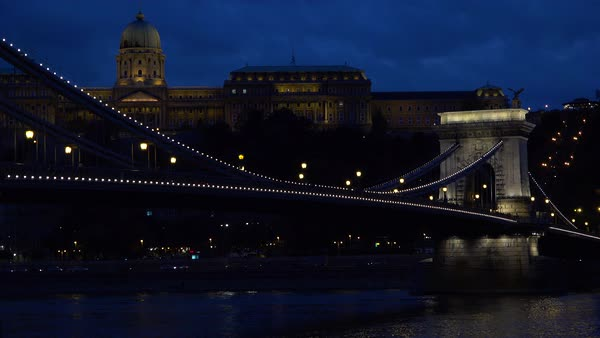Night view beside an illuminated bridge over the Danube River in Budapest, Hungary. Royalty-free stock video