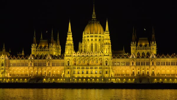 The beautiful parliament building glows in evening light along the Danube River in Budapest, Hungary. Royalty-free stock video