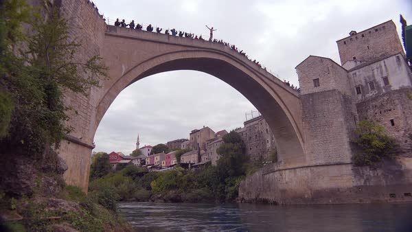 Establishing shot of the famous Stari Most bridge in Mostar, Bosnia Herzegovina with man jumping. Royalty-free stock video