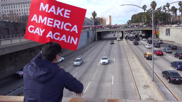 Protestors against Donald Trump stand on an overpass in Los Angeles urging people to make America gay again. Royalty-free stock video