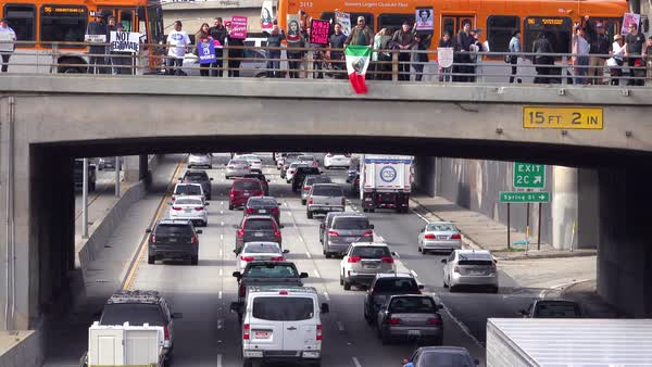 Protestors against Donald Trump stand on an overpass in Los Angeles waving Mexican flags. Royalty-free stock video