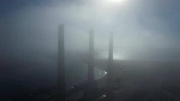 Amazing aerial over large power plant smokestacks in the fog near Morro Bay, California. Royalty-free stock video