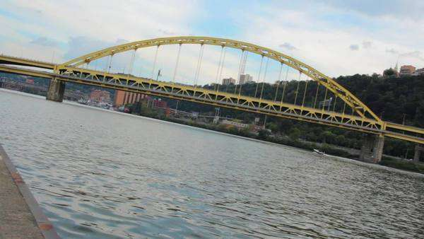 A view of the Fort Pitt Bridge over the Monongahela River in Pittsburgh, Pennsylvania, USA, featuring a busy highway with cars, boats traveling down the river and a bright yellow bridge. Wide shot from Point State Park with no camera movement. Royalty-free stock video