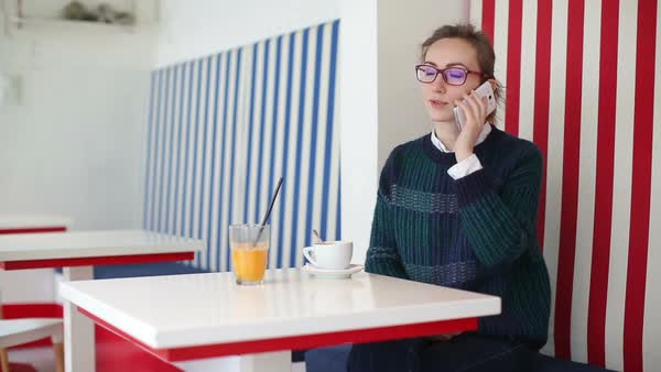 Young woman wearing sweater and eyeglasses, smiling and talking on mobile phone at the coffee shop while having a coffee. Orange juice is on the table. Medium wide shot. Royalty-free stock video