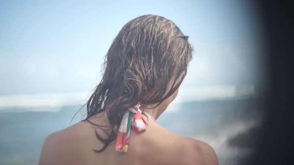 Handheld shot showing a young woman wearing a bathing suit walking on the beach Royalty-free stock video