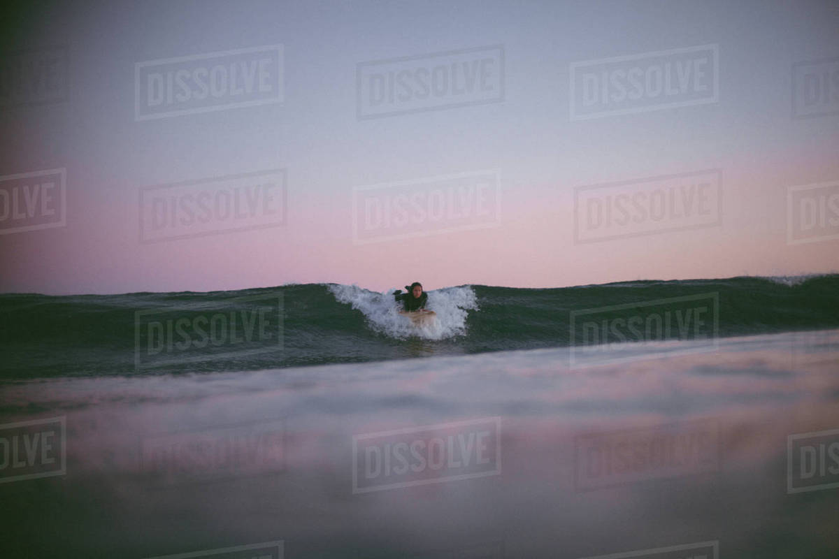 Young woman surfing in ocean at sunset Royalty-free stock photo