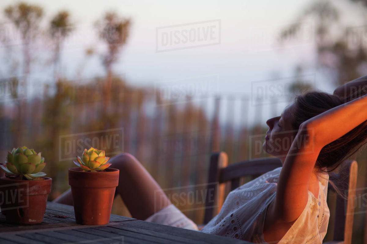 Young woman relaxing on terrace at sunset Royalty-free stock photo