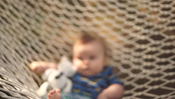 Hand-held shot of a baby lying in a hammock Royalty-free stock video