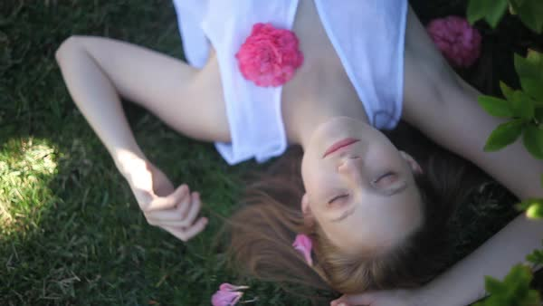 Close-up shot of a woman in white blouse lounging on the grass Royalty-free stock video