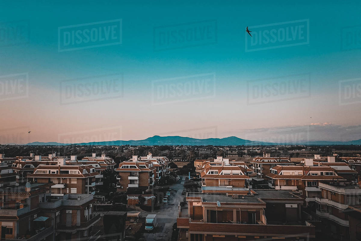 Town buildings and streets seen from a drone perspective at sunset in Italy with mountains in the background Royalty-free stock photo
