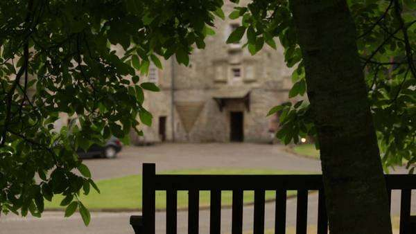 Slider shot of a bench with a tree in foreground and a castle in the background. Shot in Scotland Royalty-free stock video