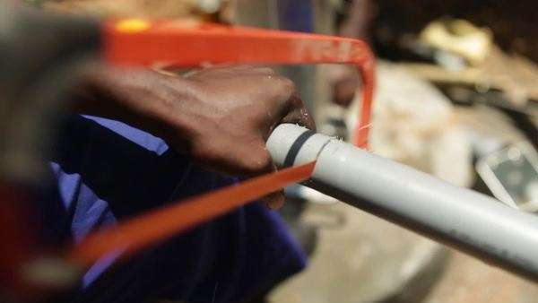 An African man sawing a plastic tube used to install a new well in rural Uganda, Africa Royalty-free stock video