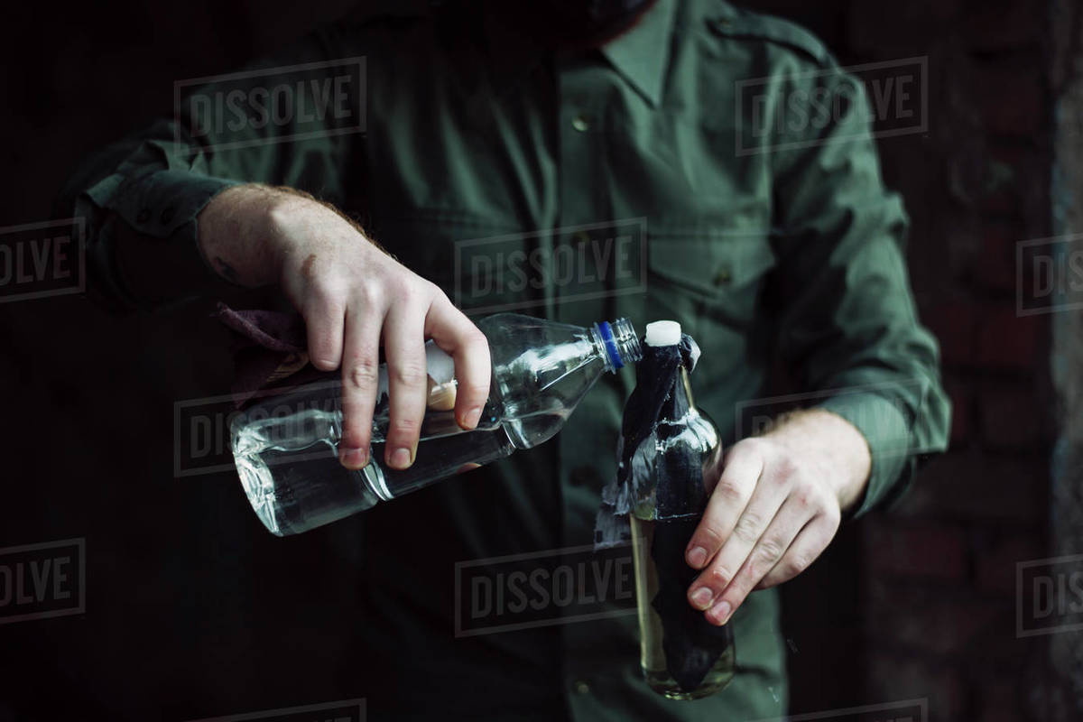 Dangerous bandit soak a wick of molotov cocktail with a fuel. Illegal weapon on the city streets. Royalty-free stock photo