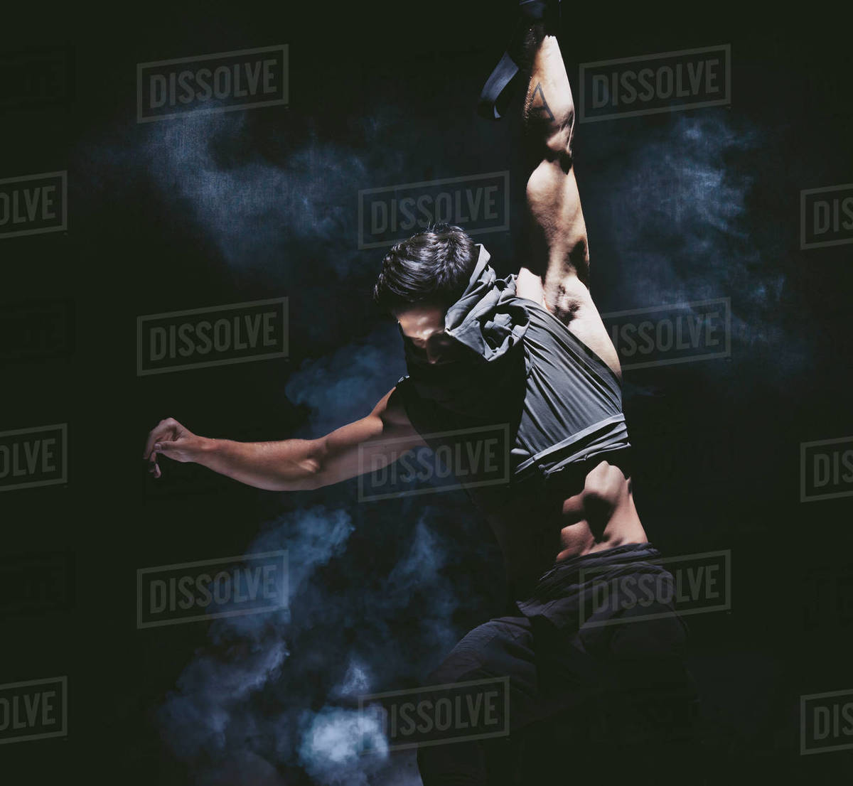 Cool brawny guy on the slings in the dark. Incredible straight scene. Royalty-free stock photo