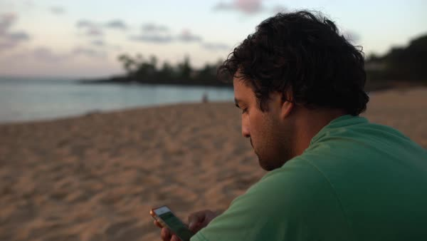 Hand-held shot of a man using a smartphone on a beach Royalty-free stock video