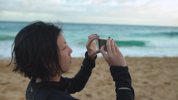 Hand-held shot of a woman taking photos on a beach Royalty-free stock video