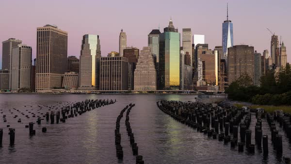 Time lapse. Lower Manhattan Financial District from Brooklyn Bridge Park with wooden piles of Pier One in the East River Royalty-free stock video