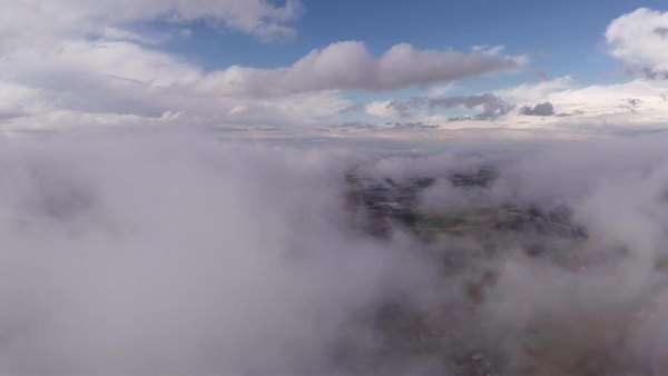 Aerial shot flying forward fast through clouds to reveal a suburban landscape below. Royalty-free stock video