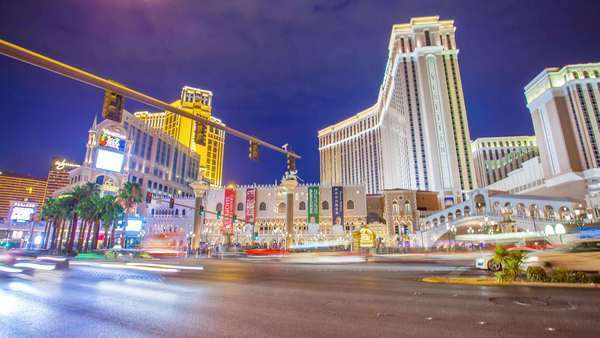 LAS VEGAS, NEVADA - JULY 10, 2014. Timelapse in motion (hyperlapse) video view on intersection at Las Vegas Strip at night. Busy traffic. View on casino Venetian. Royalty-free stock video