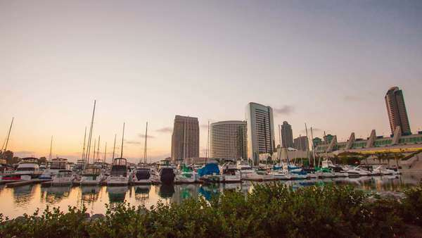 Sunset over San Diego Downtown. Timelapse in motion (hyperlapse). Shot from Embarcadero Marina Park South. View on skyscapers and yachts. Transition from day to night Royalty-free stock video