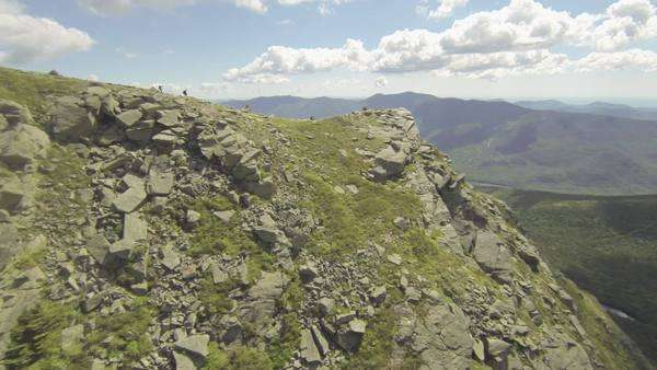 Aerial of hikers on mountain top trail in summer Royalty-free stock video