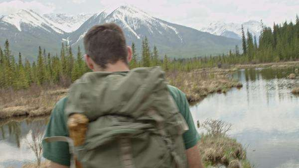 Man with backpack hikes toward small pond in front of mountains Royalty-free stock video