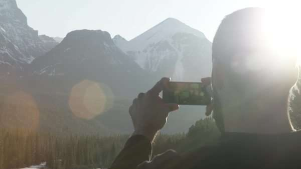 Man holds phone in front of mountains with lens flare Royalty-free stock video