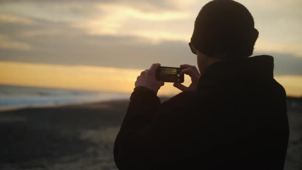 Man looking at phone then takes photo on beach at sunset Royalty-free stock video
