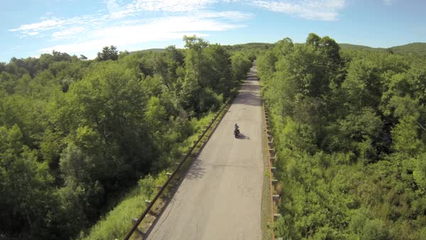 Motorcycle drives down back road Royalty-free stock video