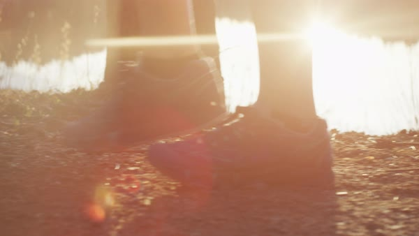 Close-up feet walking on a trail with lens flare Royalty-free stock video