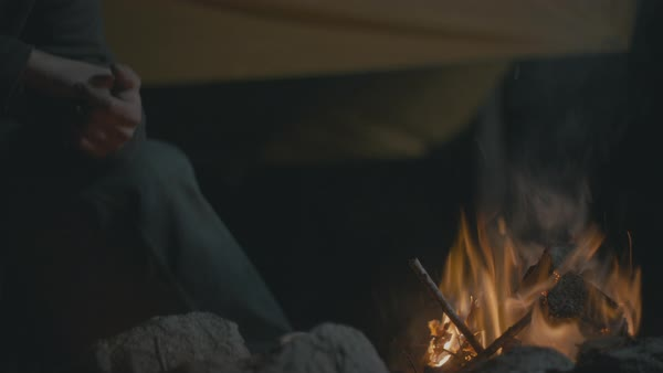 Campfire with man sitting in background Royalty-free stock video