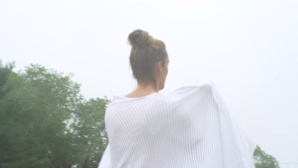 A woman wrapping herself with shawl while walking on grassy landscape Royalty-free stock video