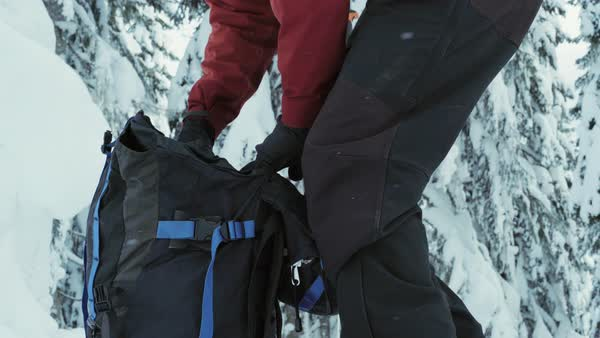 Medium shot of a ski mountaineer closing his backpack Royalty-free stock video