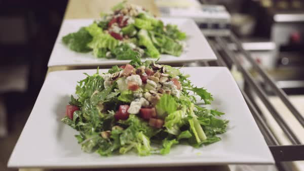 Hand-held shot of a man putting plates of salads on a counter in a restaurant Royalty-free stock video