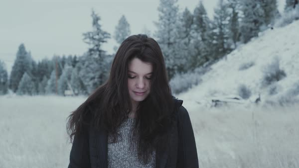 Medium shot of a young woman standing in a snow covered field Royalty-free stock video