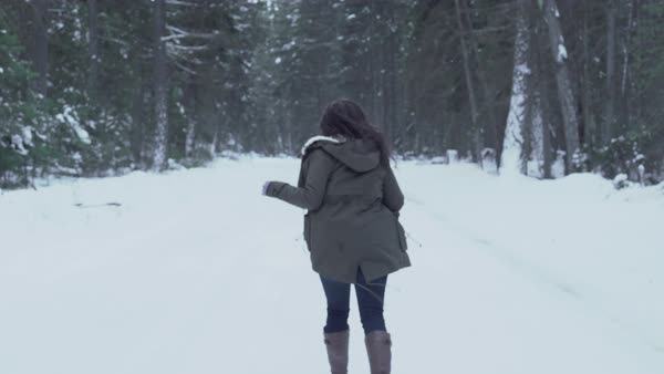 Tracking shot of a young woman running on a snow covered road Royalty-free stock video