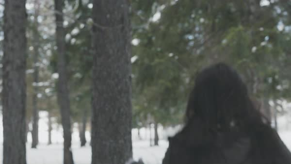 Tracking shot of a playful young woman in a winter forest Royalty-free stock video