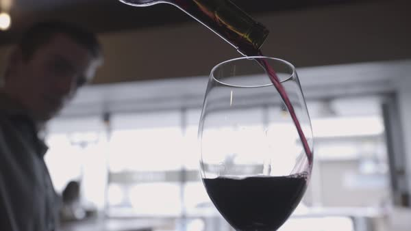 Hand-held shot view of a waiter pouring red wine into a glass Royalty-free stock video