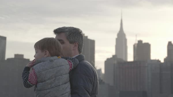 Hand-held shot of a man holding a toddler in New York Royalty-free stock video