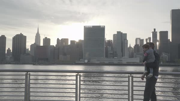Hand-held shot of a man picking up a toddler by East River Royalty-free stock video