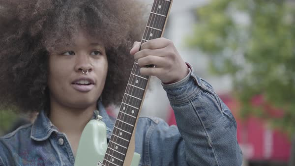 Hand-held shot of a woman playing an electric guitar on a street Royalty-free stock video