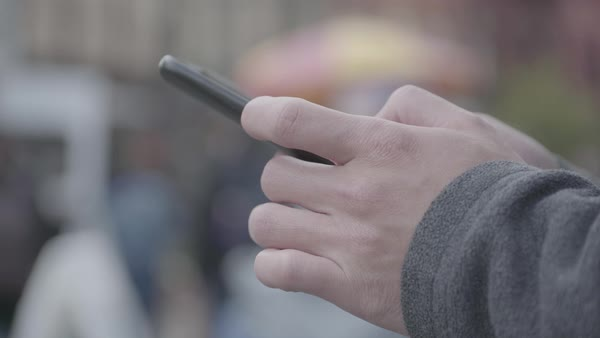 Hand-held shot of a man using his cell phone on a street Royalty-free stock video