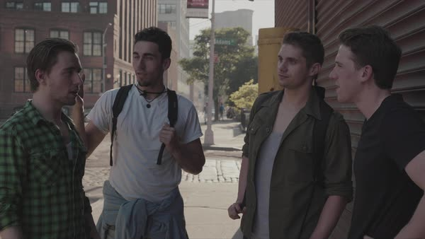 Hand-held shot of four young men talking outside Royalty-free stock video